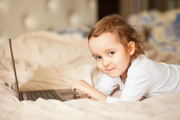 Petite fille mignonne allongée sur le lit et à l'aide d'un ordinateur portable numérique