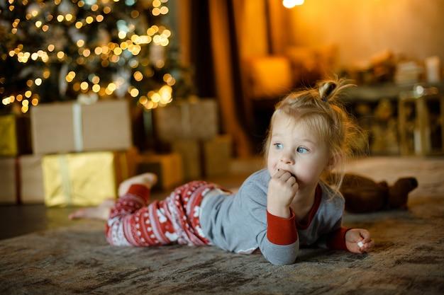 Petite fille mignonne allongée sur le tapis en pyjama en attente de noël.