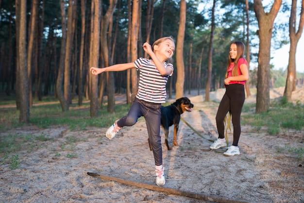 Petite fille mignonne et amusante sautant par-dessus une grande vieille branche sèche avec un large sourire sur son visage dans une forêt de pins dense par une chaude matinée ensoleillée d'été, et une soeur avec un chien se tient en arrière-plan