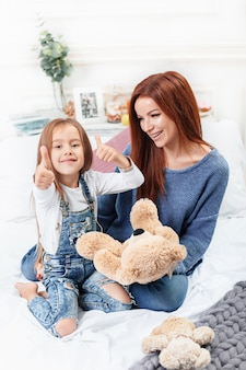 Une petite fille mignonne appréciant, jouant et créant avec des jouets avec la mère