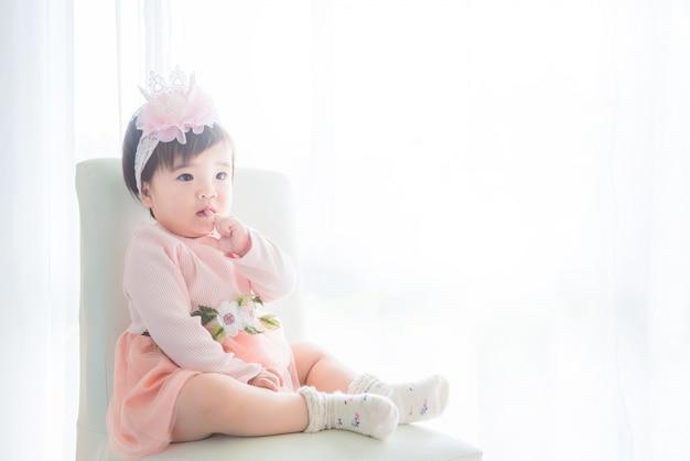 Petite fille mignonne asiatique assise sur la chaise devant une fenêtre brillante