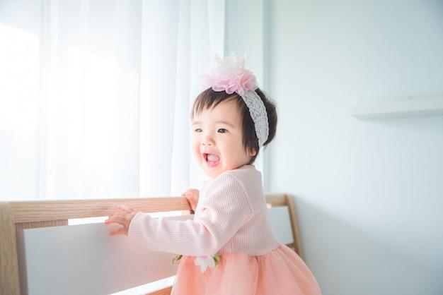 Petite fille mignonne asiatique debout et sourit sur le lit dans la chambre