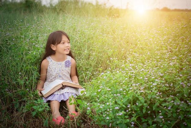 Petite fille mignonne asiatique lisant livre à la nature.