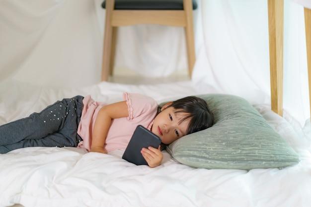 Petite fille mignonne asiatique regardant le dessin animé dans le smartphone