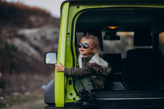 Petite fille mignonne assise à l'arrière de la voiture