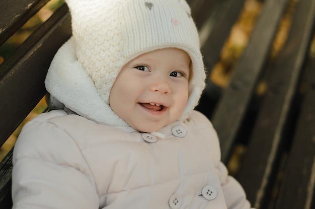 Petite fille mignonne assise sur le banc. le bébé dans la casquette et la veste sourit à l'objectif de la caméra.