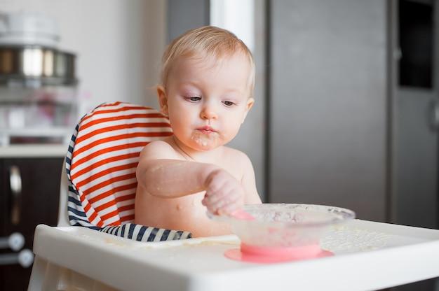 Petite fille mignonne assise sur une chaise haute et apprendre à manger avec une cuillère elle-même. drôle drôle