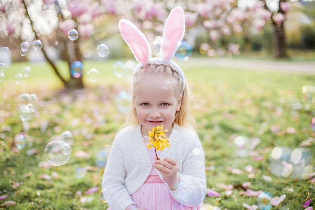 Petite fille mignonne assise sur l'herbe près du magnolia. une fille habillée en lapin de pâques tient une fleur et un œuf. printemps.