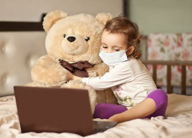 Petite fille mignonne assise sur le lit et à l'aide d'un ordinateur portable tablette numérique. appelez des amis ou des parents en ligne.