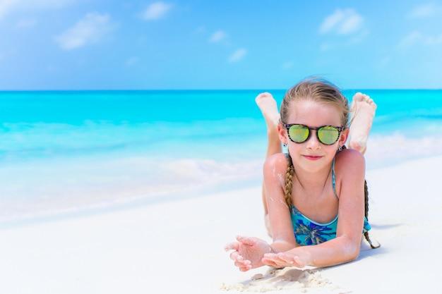 Petite fille mignonne au bord de la mer profiter de vacances à la plage