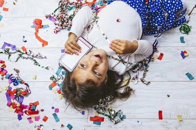 Petite fille mignonne et belle avec des confettis multicolores sur le sol avec un téléphone portable