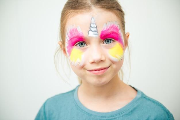 Petite fille mignonne caucasienne avec la peinture de visage de licorne