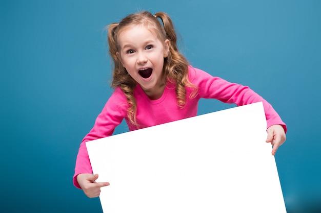 Petite fille mignonne en chemise rose avec un singe et un pantalon bleu tenir une plaque vierge vierge
