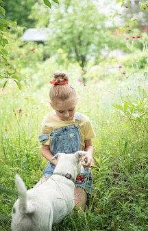La petite fille mignonne choisit une cerise d'un arbre dans le jardin de cerise