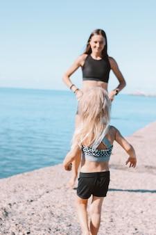 Petite fille mignonne en cours d'exécution pour s'adapter à maman sur la plage