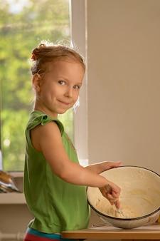 Petite fille mignonne cuisine sur cuisine. s'amuser tout en faisant des gâteaux et des biscuits.