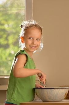 Petite fille mignonne cuisine dans la cuisine. profitez de faire des cookies. expression surprise qu'elle a été photographiée