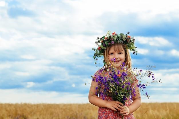 Petite fille mignonne dans le champ de blé d'été