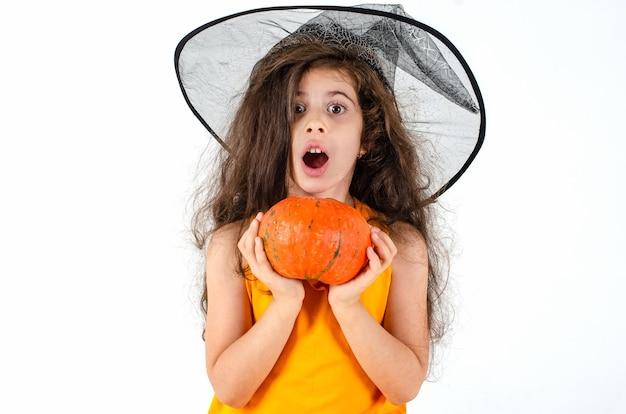 Petite fille mignonne dans un chapeau de sorcière broom pumpkin heluin place pour le texte