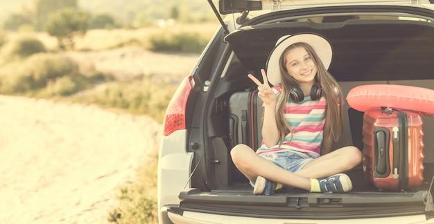 Petite fille mignonne dans le coffre d'une voiture avec des valises