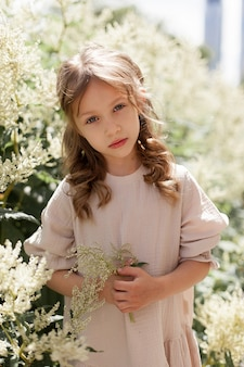 Une petite fille mignonne dans une robe beige dans la rue un jour d'été avec des fleurs dans ses mains dans le parc sur fond de fleurs. le bébé regarde la caméra et est triste. une promenade au grand air.