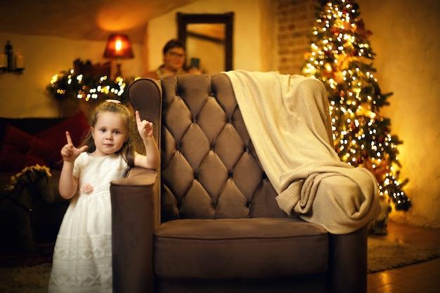 Petite fille mignonne dans une robe blanche posant près du fauteuil dans l'intérieur de nouvelle année