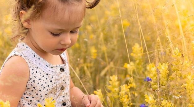 Petite fille mignonne dans une robe légère 1-3 dans le domaine des épillets de seigle en été