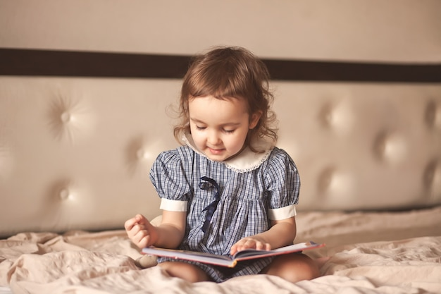 Petite fille mignonne dans une robe rétro en lisant un livre.