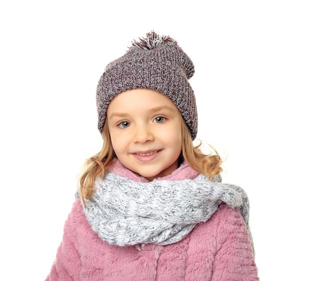 Petite fille mignonne dans des vêtements chauds sur le fond blanc