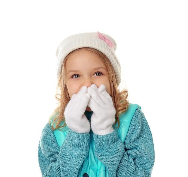 Petite fille mignonne dans des vêtements chauds sur le mur blanc
