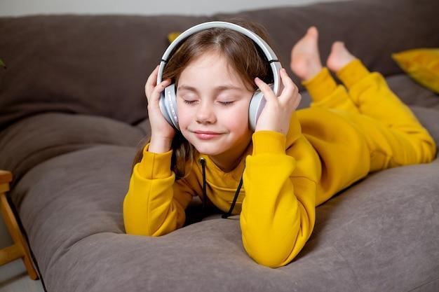 La petite fille mignonne dans des vêtements jaunes se trouve sur le lit et écoute de la musique