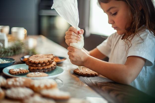 Petite fille mignonne décore le pain d'épice avec du glaçage au sucre. préparation pour le concept de noël.