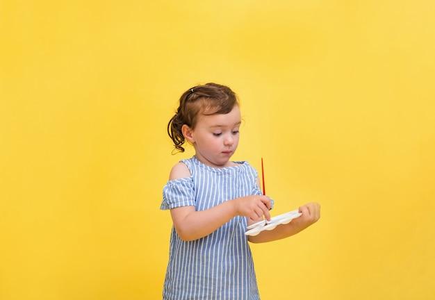 Une petite fille mignonne dessine avec une brosse avec un fouet dans ses mains sur un fond jaune avec un espace pour le texte.