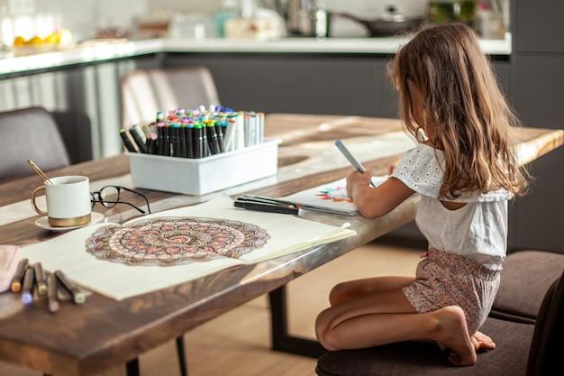 Une petite fille mignonne dessine un motif de mandala circulaire dans l'album avec des marqueurs d'art