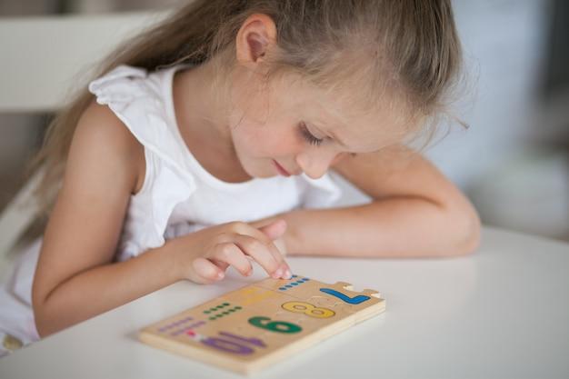 Petite fille mignonne enfant d'âge préscolaire jouant à des jeux éducatifs avec du bois