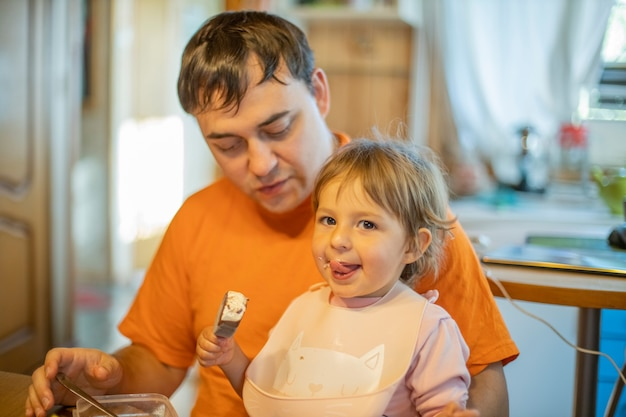 Petite fille mignonne d'enfant en bas âge mangeant la glace à l'eau glacée se reposant sur le recouvrement de papa, foyer mou.