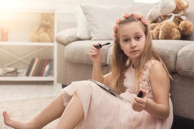 Petite fille mignonne essayant les cosmétiques de sa maman. joli gosse se teintant les cils avec du mascara, assis sur un tapis au sol parmi de nombreux produits de beauté. petite fashionista faisant du maquillage, espace de copie