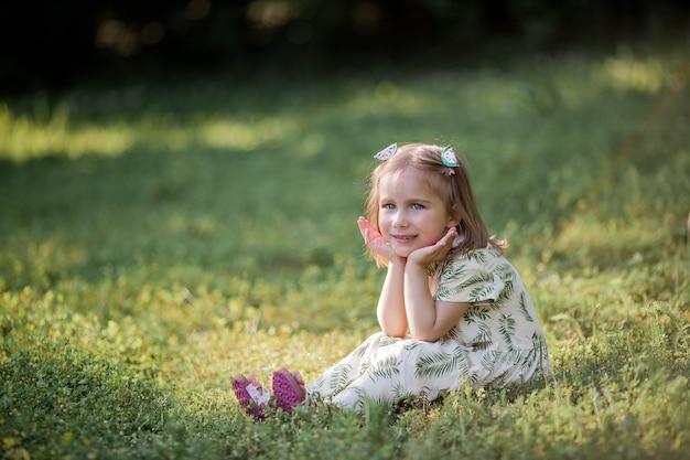 Petite fille mignonne est assise sur l'herbe. fille heureuse dans le parc. été.