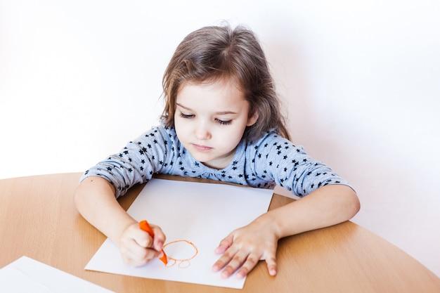 Une petite fille mignonne est assise à une table et dessine