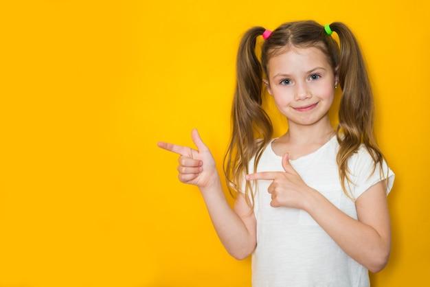 Une petite fille mignonne est attirée par l'attention pointant du doigt quelque chose.