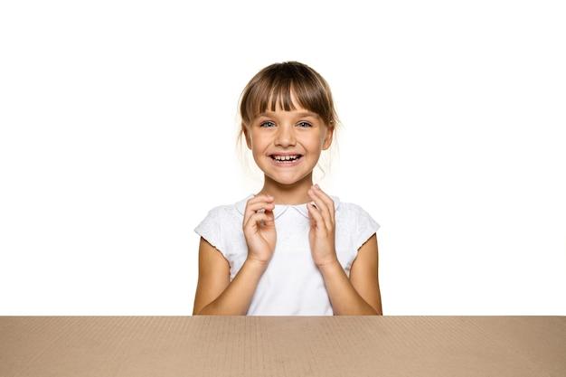 Petite fille mignonne et étonnée ouvrant le plus gros colis postal.
