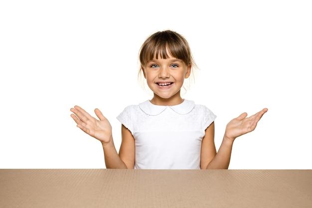 Petite fille mignonne et étonnée ouvrant le plus gros colis postal