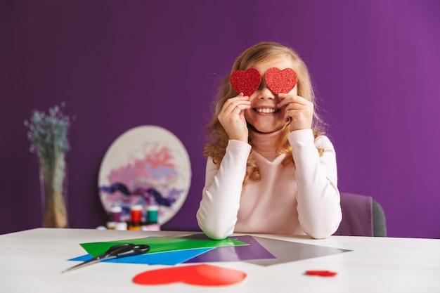 Petite fille mignonne faisant un coeur du papier à la table