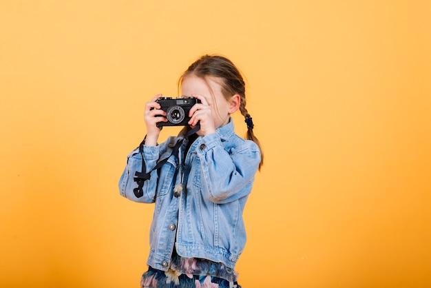 Une petite fille mignonne faisant la photo sur un mur jaune.