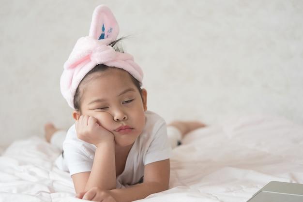 Une petite fille mignonne fait une grimace. elle n'est pas heureuse avec quelque chose.