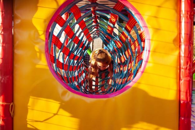 Petite fille mignonne grimpe à travers un long tunnel lumineux profitant des vacances d'été