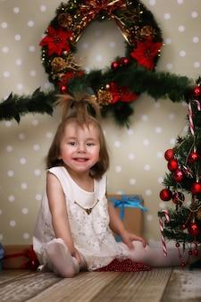 La petite fille mignonne habille l'arbre de noël sur le sol dans la chambre