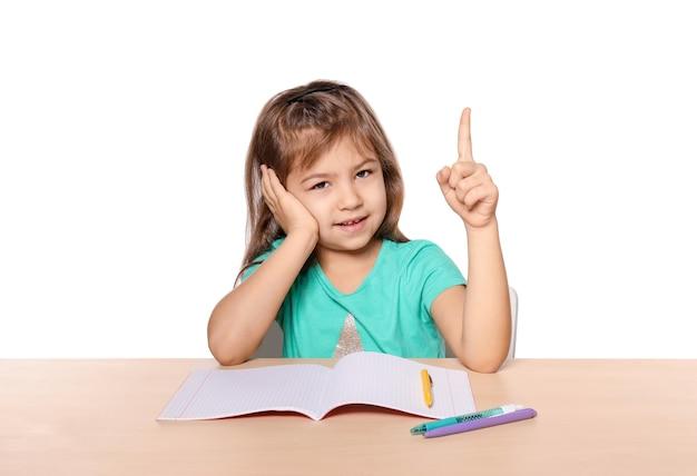 Petite fille mignonne avec l'index augmenté contre le blanc. enfant faisant ses devoirs