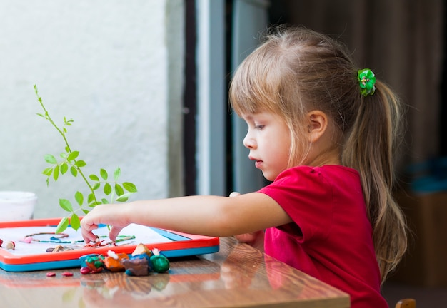 Petite fille mignonne jouant à la table jouer dehors