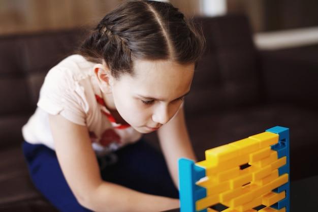 La petite fille mignonne joue à un jeu de société de briques en plastique jaunes